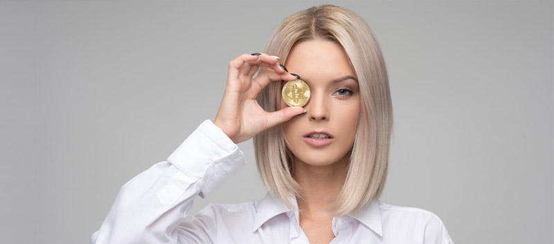 Woman holding bitcoin near eye