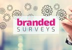 Branded Surveys logo superimposed on man writing on clear whiteboard