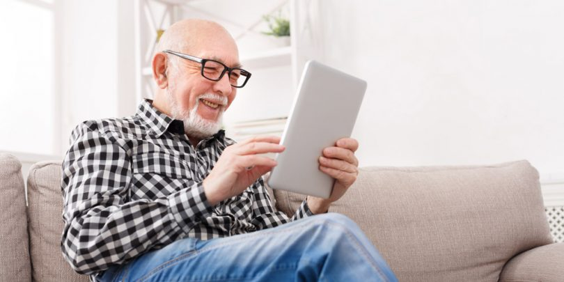 Senior citizen man taking surveys on his tablet