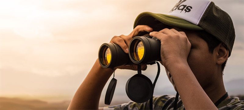 Man using binoculars for searching