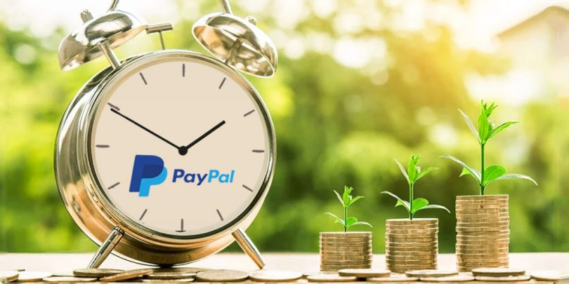 Clock with PayPal logo next to stack of coins