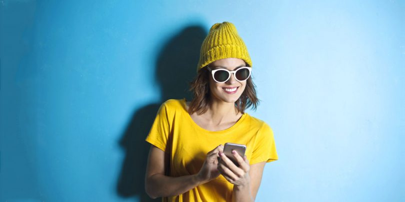 Woman wearing yellow taking an online survey on her phone