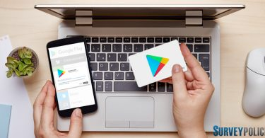 Woman entering google play gift card onto phone