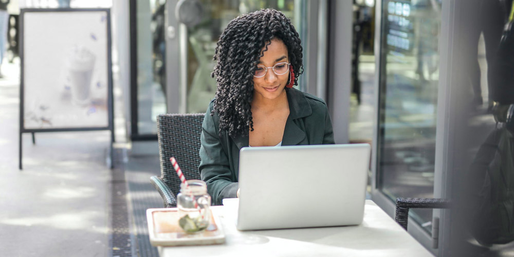 Woman watching videos on laptop at cafe