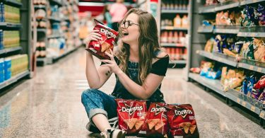 Woman sitting on floor of CVS holding chips