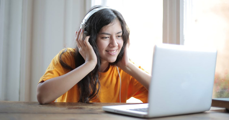 Teen listening to music on computer