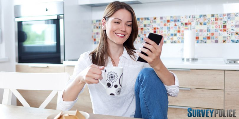 Woman in kitchen looking at surveys on her phone