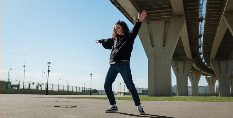 Woman dancing under bridge