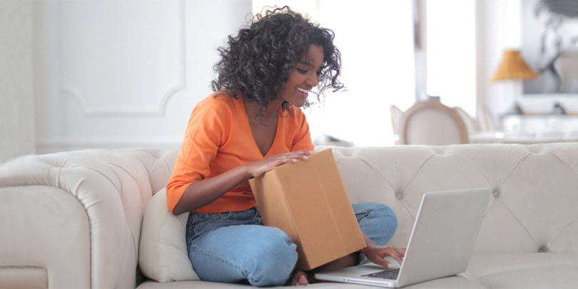 Woman with product testing box in font of computer